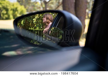 Reflection of happy teenage girl in wing mirror standing beside a car