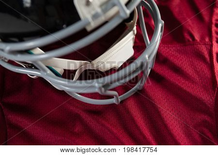 Close up of sports helmet on maroon jersey