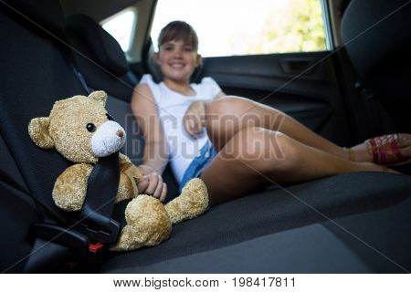 Happy teenage girl sitting with teddy bear in the back seat of car