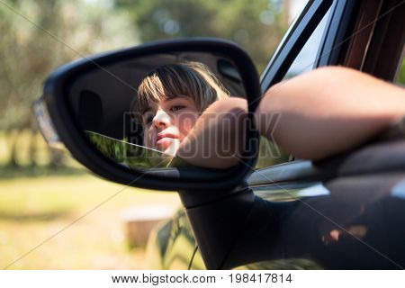 Reflection of thoughtful teenage girl in wing mirror of a car