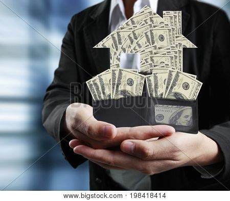Businessman holding full American dollar wallet with money house model in human hands