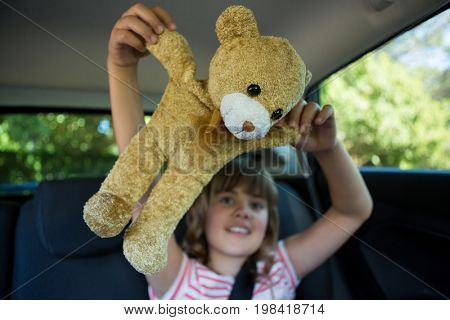 Happy teenage girl playing with teddy bear in back seat of car