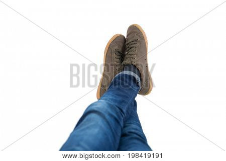 Low-section of teenage boy lying with legs crossed at ankle on white background