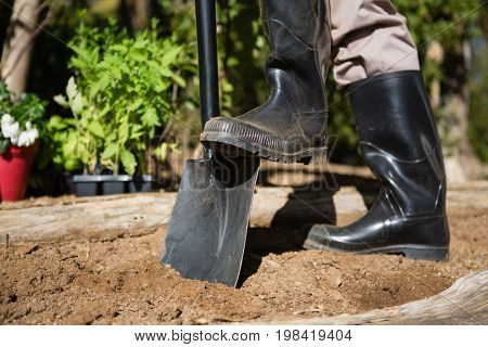 Low section of man standing with shovel in garden on a sunny day