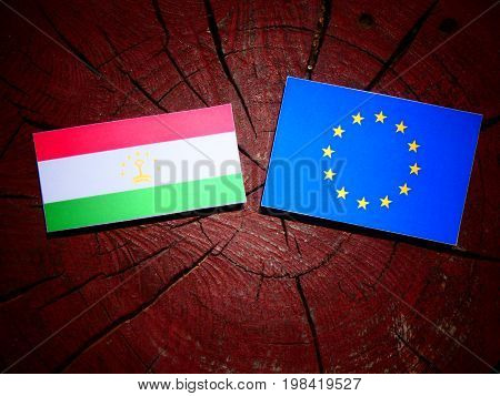 Tajikistan Flag With Eu Flag On A Tree Stump Isolated