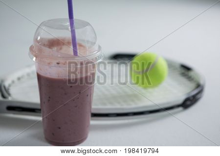 Close up of smoothie by racket and tennis ball on white background