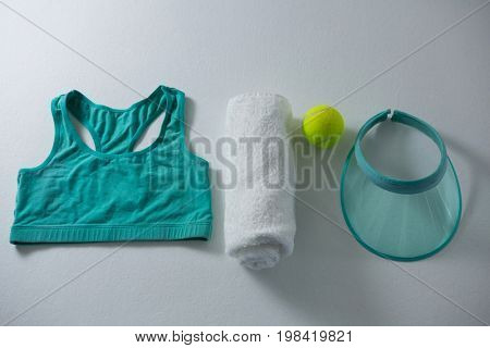 Sports bar with napkin and tennis ball by sun visor on white background