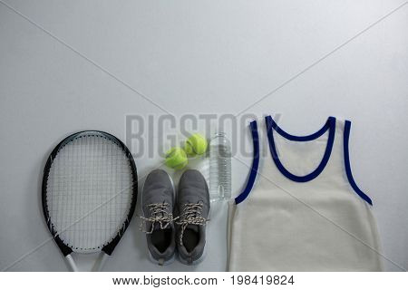 Racket with ball and sports shoe by vest on white background
