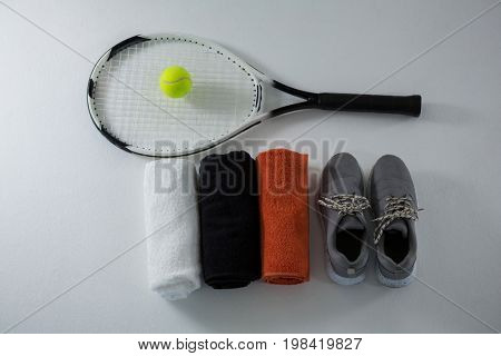 Overhead view of ball on racket by napkins and sports shoe over white background