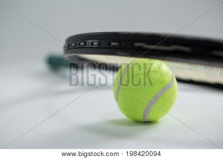 Close up of racket on tennis ball against white background