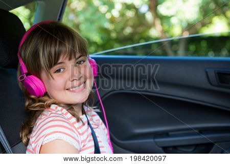 Portrait of smiling teenage girl with headphones in the back seat of car