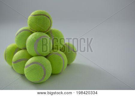 Heap of fluorescent tennis balls against white background