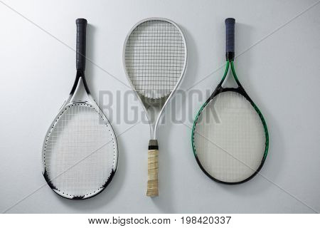 Directly above shot of metallic tennis rackets on white background