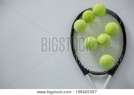 Overhead view of tennis balls on racket against white background