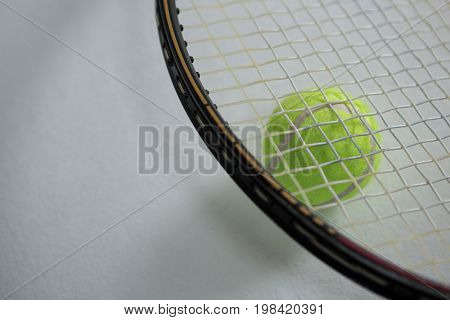High angle view of racket on tennis ball against white background