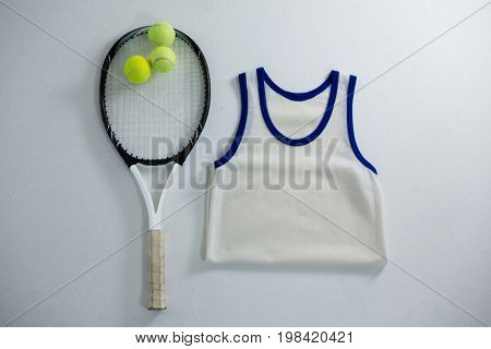 Overhead view of racket with tennis balls by vest on white background