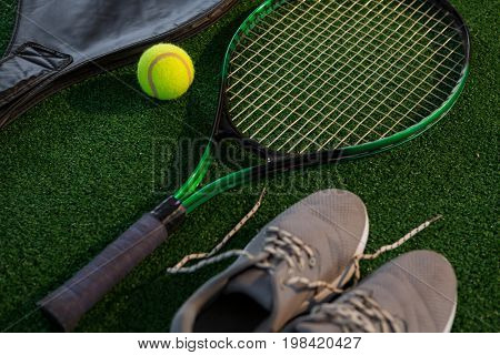 Close up of racket with ball and sports shoes on court