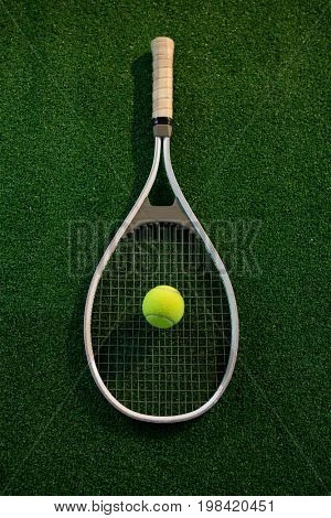 Directly above shot of racket and tennis ball on field