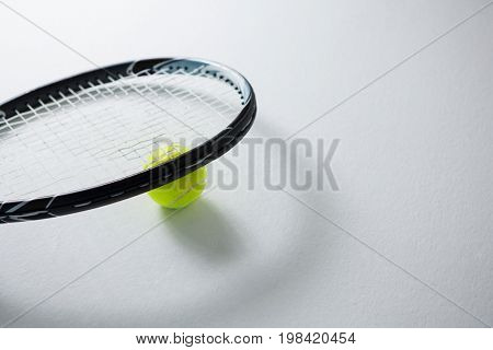 Cropped image of racket with tennis ball on white background