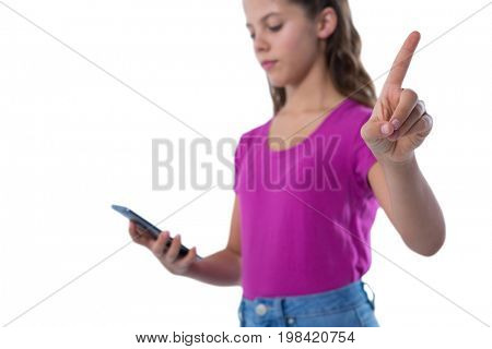 Teenage girl gesturing while using mobile phone against white background