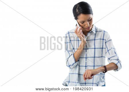 Female executive looking at her wristwatch while talking on the phone against white background