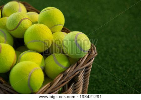 Close up of tennis balls in wicker basket on field