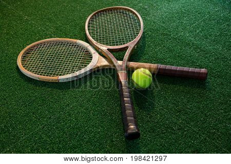 Close up of wooden rackets with tennis ball on playing field