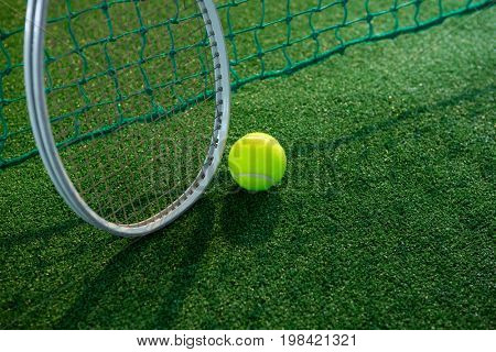 High angle view of tennis ball with racket by net on court