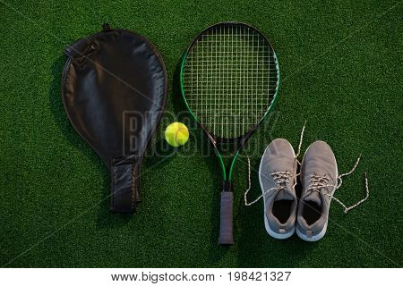 Directly above shot of racket with ball and sports shoes on field
