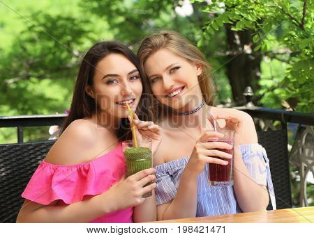 Two attractive ladies enjoying fresh smoothie in cafe