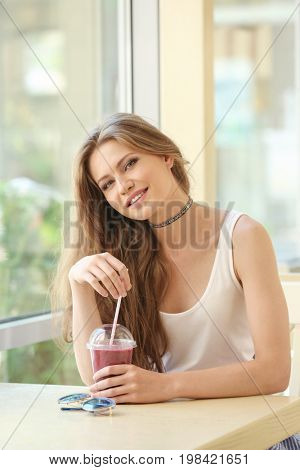 Attractive young woman sitting in cafe and drinking fresh smoothie