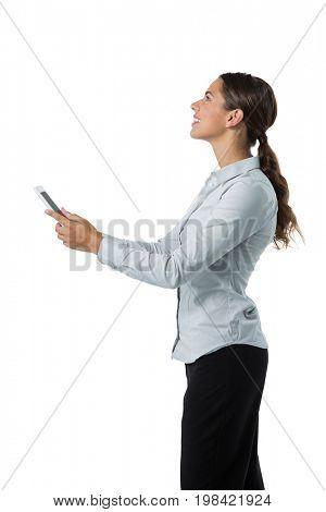 Smiling female executive using digital tablet against white background