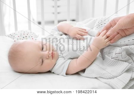 Cute baby lying in cradle and holding mother's hand. Insomnia and sleep disorders concept