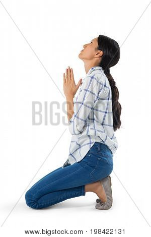 Side view of woman praying against white background