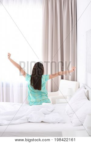 Young beautiful woman awaking in light hotel room