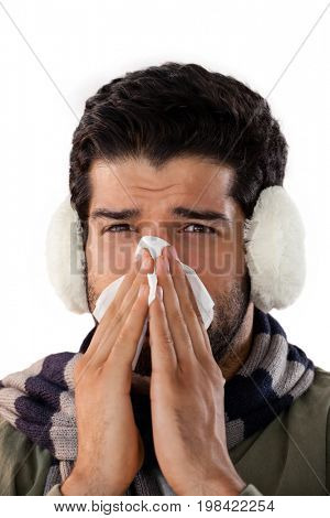 Man blowing his nose with tissue paper against white background