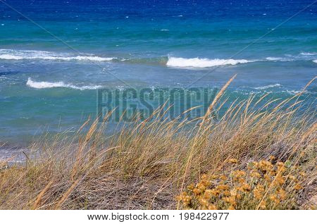Typical view of cyclades islands nature dry beige grass and turquoise blue sea