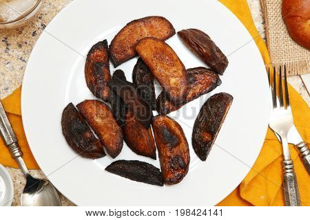Burnt Potato Wedges in a plate on a table.