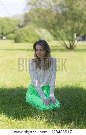 Slender girl on grass in summer park