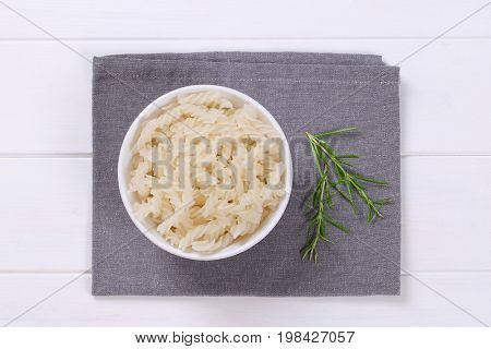 bowl of cooked rice pasta fusilli on grey place mat