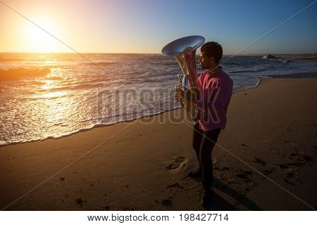Musician playing the Tuba on the sea coast at sunset. Romantic photo.