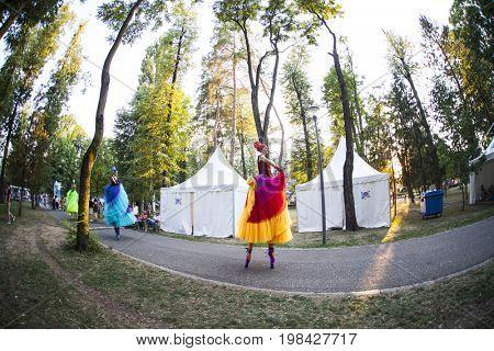 Cluj-Napoca, Romania - August 3, 2017:  Young girls on stilts and colorful dresses entertaining the participants at Untold Festival, one of the biggest music festivals in Europe