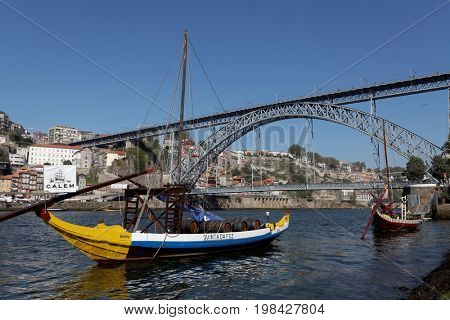 Porto,Portugal - June 6, 2016: an old portuguese boat on Douro river in front of the Dom Luís I bridge.