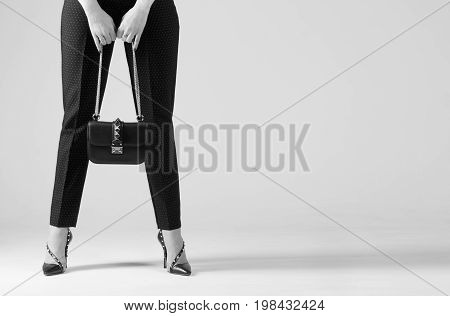 Fashionable girl in the studio dressed in pants and high-heeled shoes. Black and white style