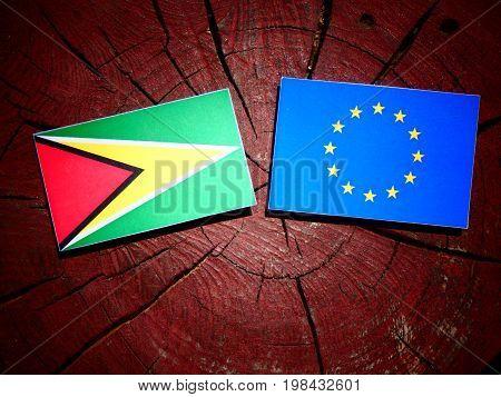 Guyana Flag With Eu Flag On A Tree Stump Isolated