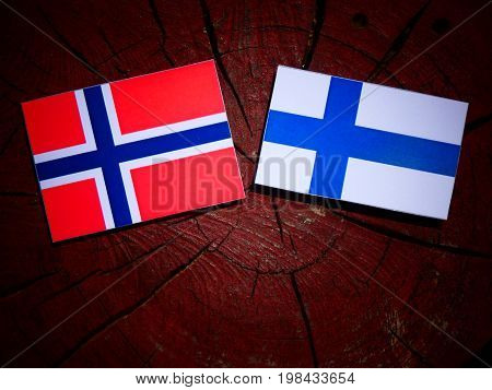 Norwegian Flag With Finnish Flag On A Tree Stump Isolated
