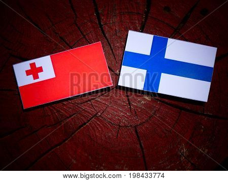 Tongan Flag With Finnish Flag On A Tree Stump Isolated