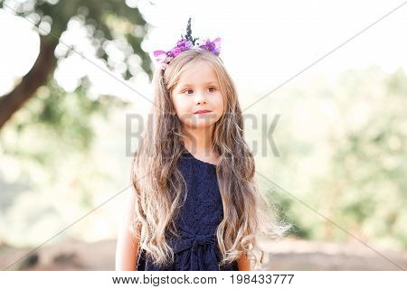 Cute baby girl 4-5 eyar old wearing dress and handmade headband outdoors. Looking away. Summer time.