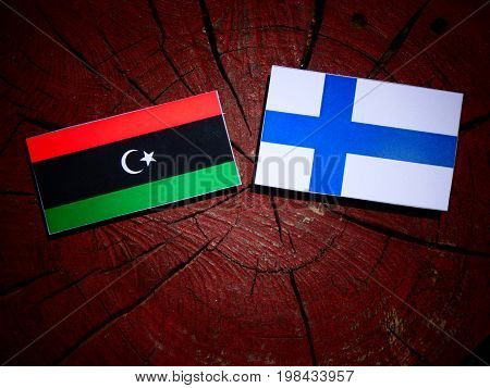 Libyan Flag With Finnish Flag On A Tree Stump Isolated