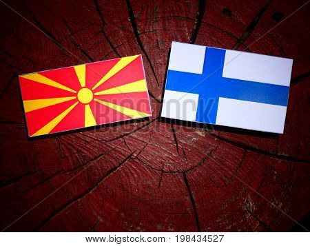 Macedonian Flag With Finnish Flag On A Tree Stump Isolated